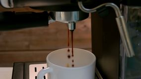 Drops of coffee dripping into a cup. Close-up of a drops of coffee dripping into a cup from a coffee machine stock video footage