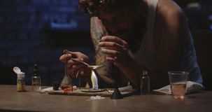 Man heating drug in a spoon. Close-up of a drug addict heating drug in a spoon over flame stock footage