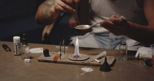 Man heating drug in a spoon. Close-up of a drug addict heating drug in a spoon over flame stock video footage