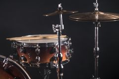 Close-up Drum set in a dark room against the backdrop of the spotlight. Atmospheric background symbol of playing rock or jazz. Drums. Copper plates on a cold stock image