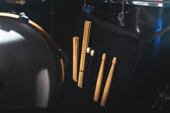 Close-up of drum sticks in a case on one of the drums in a dark studio. The concept of live performances.  stock photography