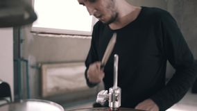 Close-up of the drummer during the game on the drum set. The camera is in motion. Close-up shows the face of the drummer. The drummer in the black jacket stock footage