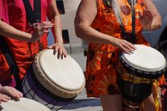 Close up of drumming by woman in bright clothes, Stock Images