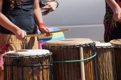 Close up of drumming by woman in bright clothes, Royalty Free Stock Image