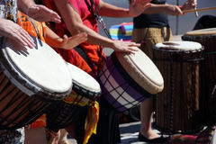 Close up of drumming by woman in bright clothes, Royalty Free Stock Photography