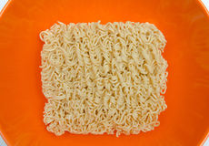 Close up Dry instant Noodle in orange bowl on the white backgrou Royalty Free Stock Photos