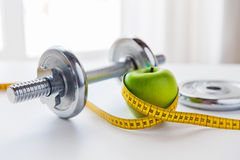 Close up of dumbbell and apple with measuring tape Royalty Free Stock Photos