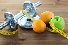 Close up of dumbbell, fruits and measuring tape Royalty Free Stock Photos