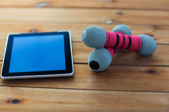 Close up of dumbbells and tablet pc on wood Stock Image