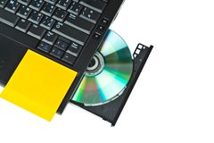Close up of a dvd in a laptop tray and post-it Stock Image