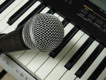 Close-up of a dynamic vocal microphone and a digital keyboard. royalty free stock photos