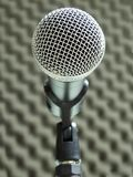Close-up of a dynamic vocal microphone. Blurred background of acoustic foam. Close-up of a dynamic hand held vocal microphone. Blurred background of gray royalty free stock photos