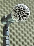 Close-up of a dynamic vocal microphone. Blurred background of acoustic foam. Close-up of a dynamic hand held vocal microphone. Blurred background of gray stock photography