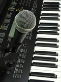 Close-up of a dynamic vocal microphone and a digital keyboard. stock image