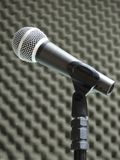 Close-up of a dynamic vocal microphone. Blurred background of acoustic foam. Close-up of a dynamic hand held vocal microphone. Blurred background of gray royalty free stock image