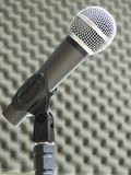 Close-up of a dynamic vocal microphone. Blurred background of acoustic foam. Close-up of a dynamic hand held vocal microphone. Blurred background of gray stock image