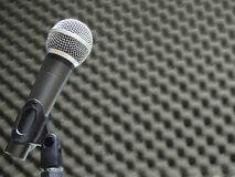 Close-up of a dynamic vocal microphone. Blurred background of acoustic foam. Close-up of a dynamic hand held vocal microphone. Blurred background of gray royalty free stock images