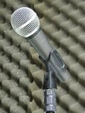 Close-up of a dynamic vocal microphone. Blurred background of acoustic foam. Close-up of a dynamic hand held vocal microphone. Blurred background of gray stock photo