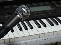 Close-up of a dynamic vocal microphone and a digital keyboard. stock photo