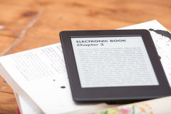 Close up of an e-book reader. Close up of an ebook reader leaning over a stack of traditional books. The text on the ebook reader is an lorem ipsum royalty free stock image