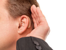 I can't hear you using hearing aid. Close up ear of a middle aged businessman wearing hearing aid and listening for a sound Stock Photos