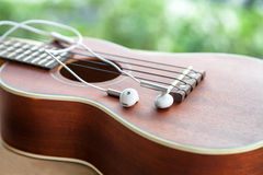 close-up of earphone with ukulele guitar on wooden table in the Stock Photos