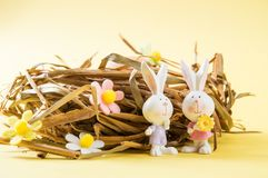 Close up. Easter card. Brown eggs in a nest of straw. Two porcelain bunnies in the foreground. The decor of the felt flowers of. Close up, macro. Easter card stock photos