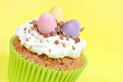 Easter cupcake with chocolate eggs on yellow background Royalty Free Stock Image