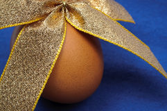 Close-up of Easter egg tied by gold ribbon. Close-up of brown Easter egg tied by gold ribbon over blue background Stock Image