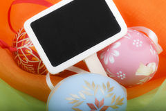Close-up of Easter eggs and blackboard on colourful velvet Stock Photos