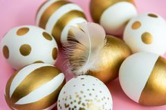 Close up of easter eggs colored with golden paint. Various striped and dotted designs. Pink background. Royalty Free Stock Images