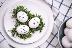 Close up. Easter table setting with white eggs in a nest. Faces are painted on the eggs