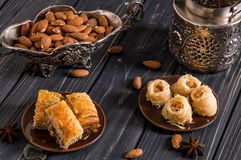Close up. Eastern still life. Assortmant traditional homemade baklava. Turkish pottery and silverware. Dark wooden background stock photography