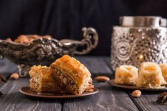 Close up. Eastern still life. Turkish traditional honey baklava, nuts. Pottery and silverware. Dark wooden background stock photography
