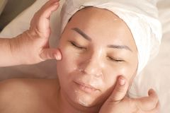 Close-up of the Eastern woman`s face. The masseur makes a facial massage with the application of cosmetic cream. Beautician hands royalty free stock images