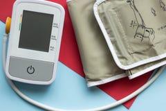 Close-up, een apparaat om bloeddruk op een blauwe en rode achtergrond te meten stock foto