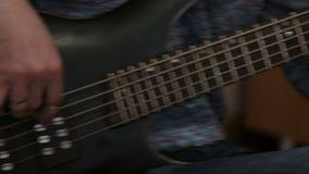 Close-up Een mens die een zwarte elektrische basgitaar speelt Muzikaal prestaties of huisoverleg stock video
