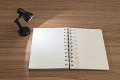 Close-up een notaboek met licht van kleine lamp in de donkere ruimte op houten bureau geweven achtergrond Stock Foto's
