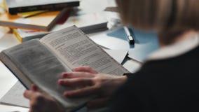 Close-up een schoolmeisje of een student die een boek lezen Zij ` s die haar thuiswerk doen stock videobeelden