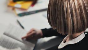 Close-up een schoolmeisje of een student die een boek lezen Zij ` s die haar thuiswerk doen stock video