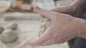 Close-up: een stuk van witte klei in de handen van vrouwenceramist stock footage