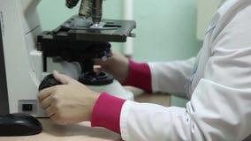 Close-up Een vrouwelijke laboratoriumtechnicus gebruikt een microscoop stock video