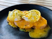 Close-up of egg Benedict with ham and french toast on a black plate for breakfast stock photo