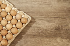 Close up eggs in carton package on a wooden table for baking. Close up eggs in carton package on a wooden table Stock Photo