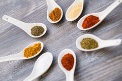 Close up of eight ceramic spoons arranged to a star with colorful spices Stock Photos