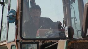 Close-up elderly male farmer sits in agricultural tractor, then starts driving to start working
