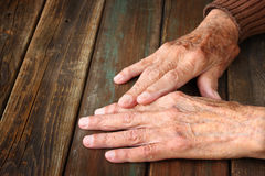 Close up of elderly male hands on wooden table Royalty Free Stock Image
