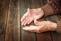 Close up of elderly male hands on wooden table Stock Images