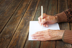 Close up of elderly male hands on wooden table . writing on blank paper Royalty Free Stock Photography