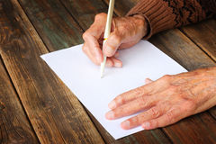 Close up of elderly male hands on wooden table . writing on blank paper Royalty Free Stock Photos